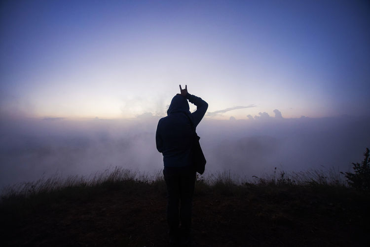 Rear view of silhouette woman standing on mountain against sky during sunset