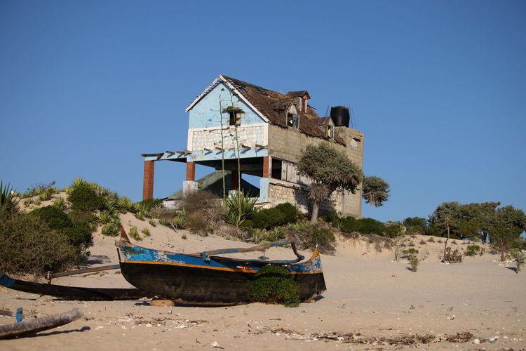 Traditional building on beach against clear sky