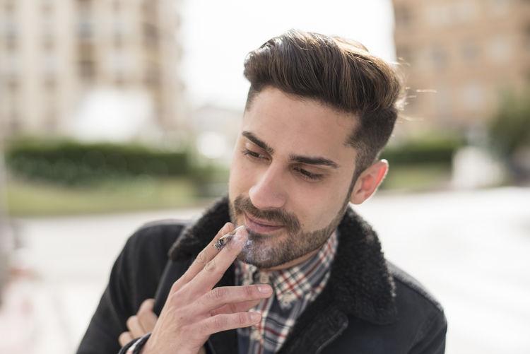 Close-up of young man smoking marijuana
