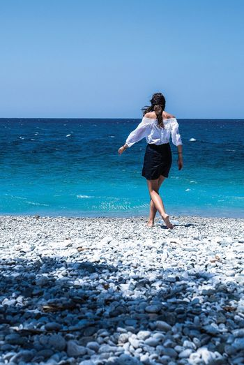 Rear view of young woman walking on beach against clear sky