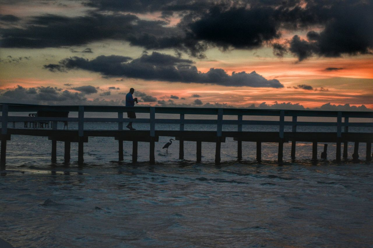 Man Walking On Pier Over Sea During Sunset