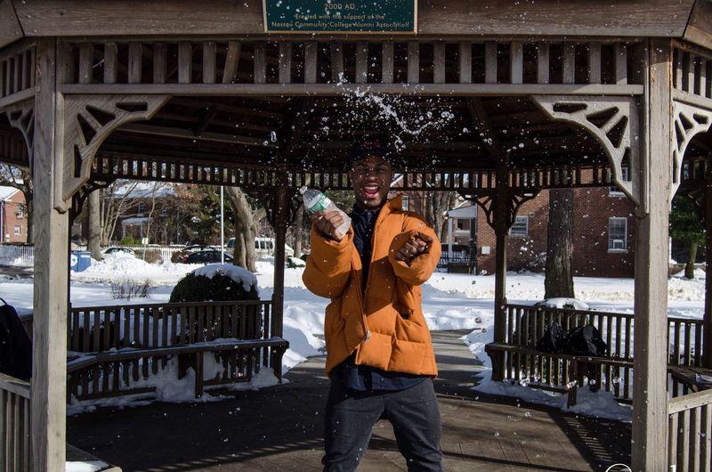 Cheerful man splashing water from bottle at gazebo during winter