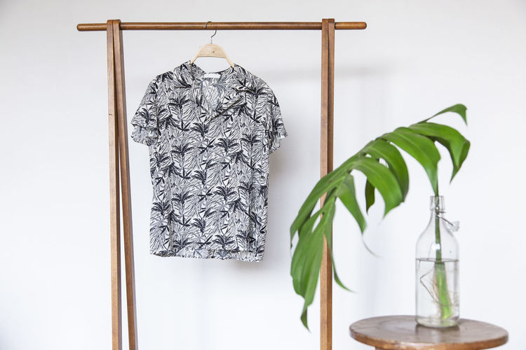 Tropical shirt Hawaii cotton on wooden hanger. Indoors  No People Leaf Close-up Table Still Life Wood - Material Plant Part White Background Nature Hanging Studio Shot Green Color Plant White Color Home Interior Focus On Foreground Transparent Glass - Material Wall - Building Feature Hawaii Shirt