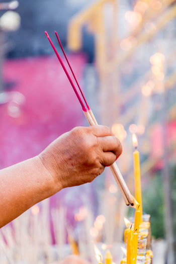 Close-up of hand lighting incenses