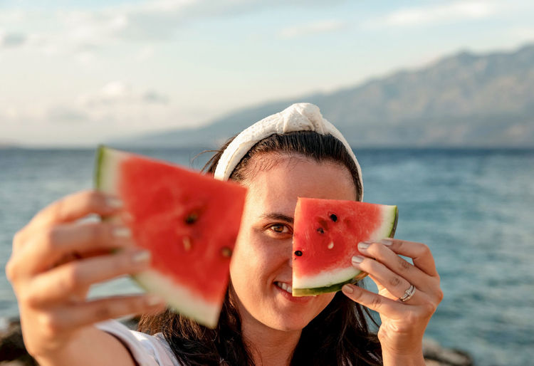 Portrait of happy young woman holding piece of watermelon in front of face.