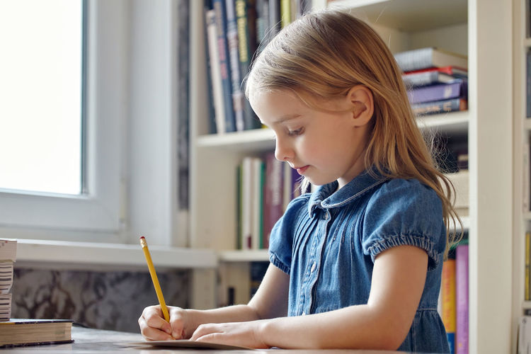 Girl writing in book at home