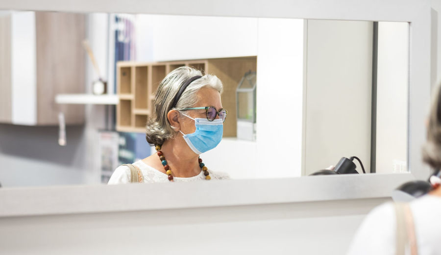 Woman wearing mask reflecting in mirror