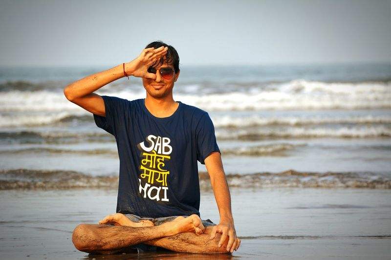 Full length of wet young man practicing yoga at beach