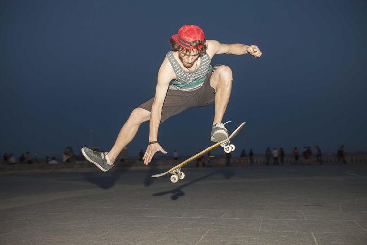 Full length of man jumping on skateboard against sky