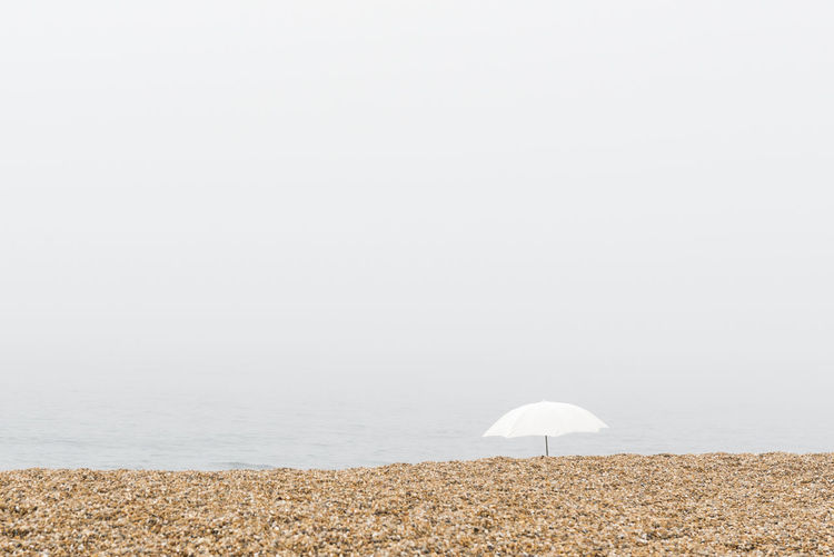 Umbrella at beach against clear sky