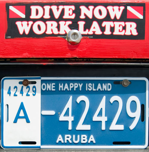 Dive Now Work Later Aruba Dive Now Diving Oranjestad Red Sign Sticker Water Sport Work Later Blue Caribbean Close-up Dive Dive Flag Message No People Number Plate One Happy Island Sign Text Underwater