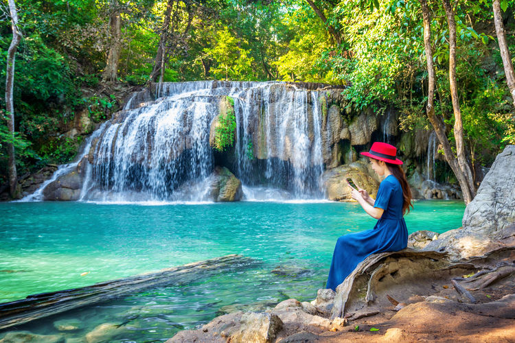 Woman sitting at Erawan waterfall in Thailand. Beautiful waterfall with emerald pool in nature. Water Waterfall Rock Rock - Object Solid Motion Tree Nature One Person Beauty In Nature Leisure Activity Scenics - Nature Plant Flowing Water Lifestyles Sitting Day Long Exposure Outdoors Looking At View