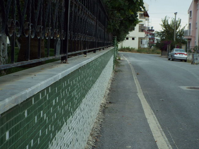 Tiled wall outside Side Fatih Camii mosque Tiled Wall Railing Trees Road Car Mosque Pavement
