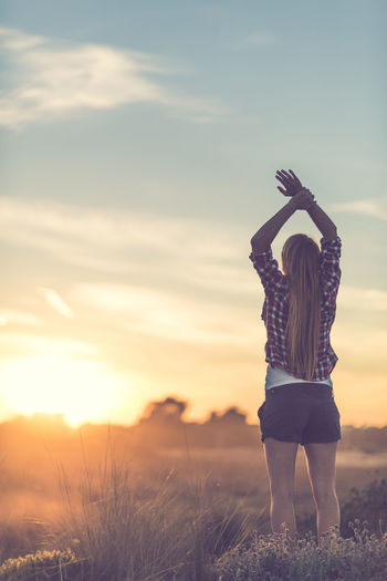 Young woman with arms raised in the sunset Freedom Adult Arms Raised Beauty In Nature Day Field Full Length Leisure Activity Lifestyles Nature One Person Outdoors People Real People Rear View Relax Relaxation Sky Standing Sunset Women Young Adult Young Women