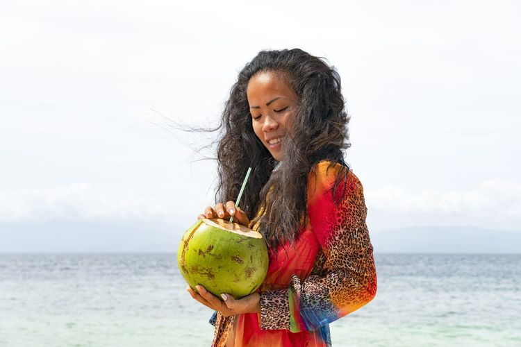 Young woman holding coconut water at beach against sky