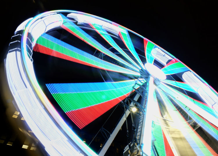 a long exposure motion blur of a spinning ferris wheel at night illuminated in bright neon colors Ferris Wheel Amusement Park Illuminated Amusement Park Ride Night Arts Culture And Entertainment Multi Colored Low Angle View Architecture Spinning Building Exterior City Built Structure No People Glowing Pattern Sky Lighting Equipment Outdoors Carnival
