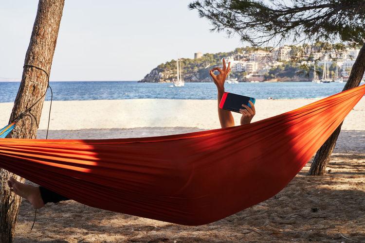 Man on hammock at beach against sky