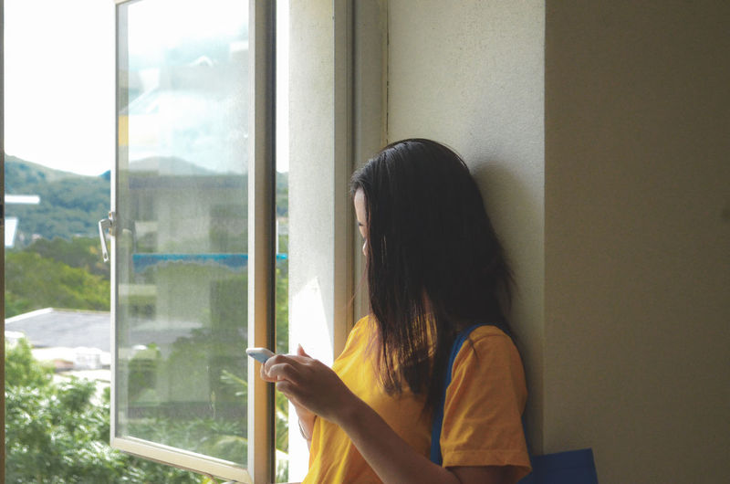 Young woman using mobile phone by window at home