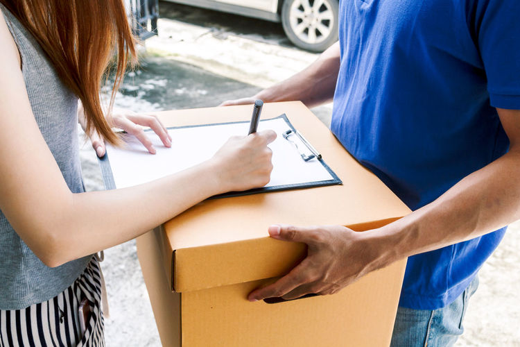 Woman putting signature in clipboard on cardboard box with delivery man Delivery Adult Box Box - Container Cardboard Cardboard Box Casual Clothing Communication Holding Indoors  Lifestyles Midsection Occupation Pen People Real People Side View Standing Two People Women Young Adult Young Women