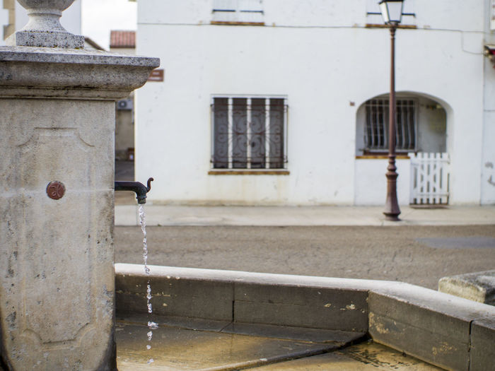Architecture Built Structure Building Exterior Building Day Faucet Focus On Foreground Water Outdoors No People Metal Motion Tap Fountain Window Safety Nature Residential District Street Running Water