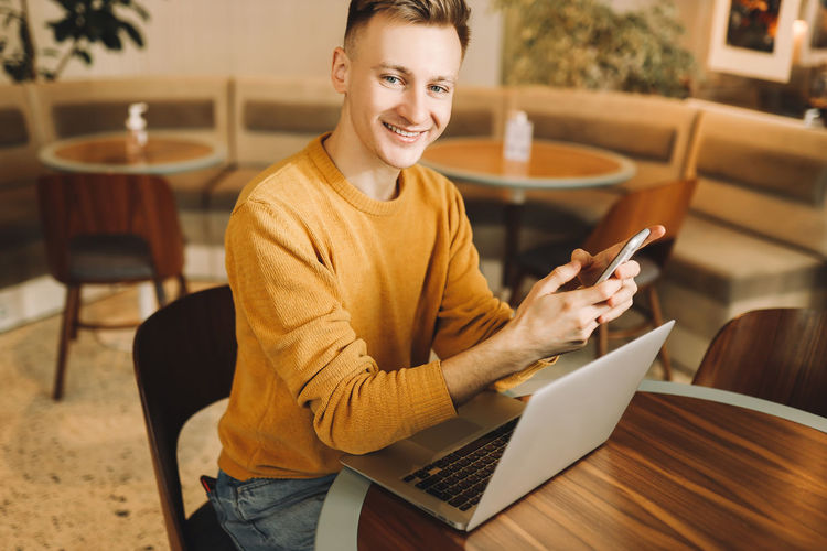 Portrait of smiling young man using mobile phone while sitting on table