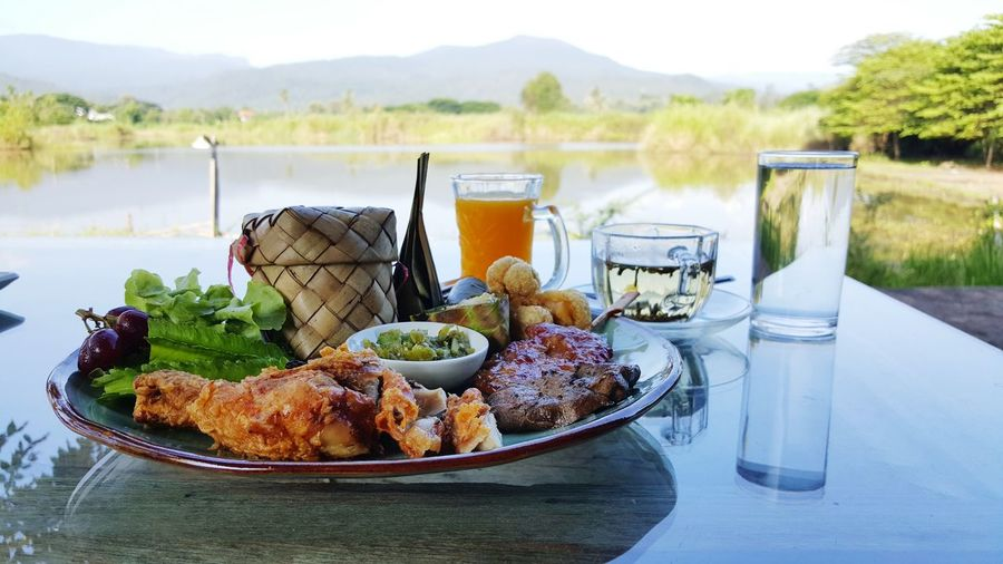 Plate of meal by glass of juice and water served on table overlooking mountains