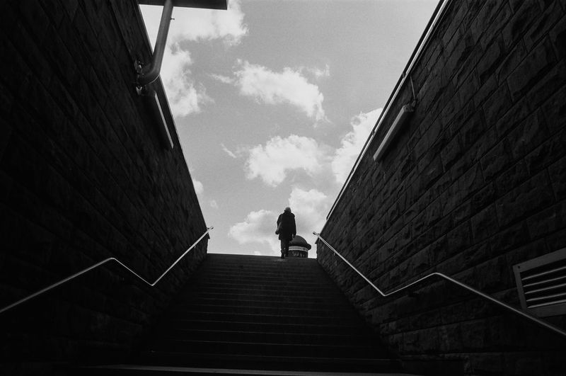 ANALOG: Ilford FP4 125 The Week on EyeEm Capture The Moment Monochrome Film Photography Analogue Photography Street Photography Light And Shadow Black And White Architecture Staircase One Person Built Structure Low Angle View Steps And Staircases Railing Sky Direction Building Exterior Day Cloud - Sky Real People Nature The Way Forward Lifestyles Full Length Outdoors Building Streetwise Photography The Art Of Street Photography