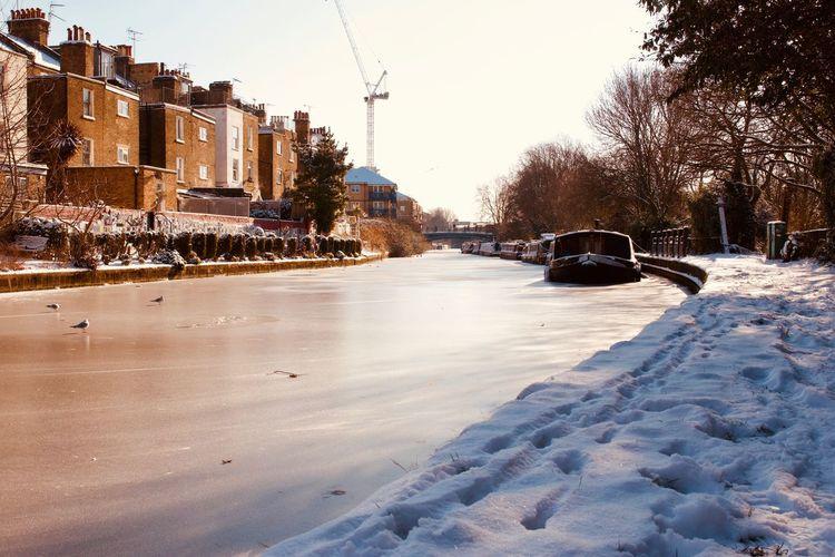 Snow covered city street against clear sky