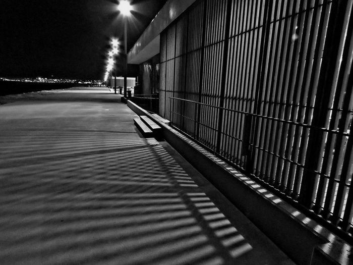 Shadow of railing on illuminated walkway at night