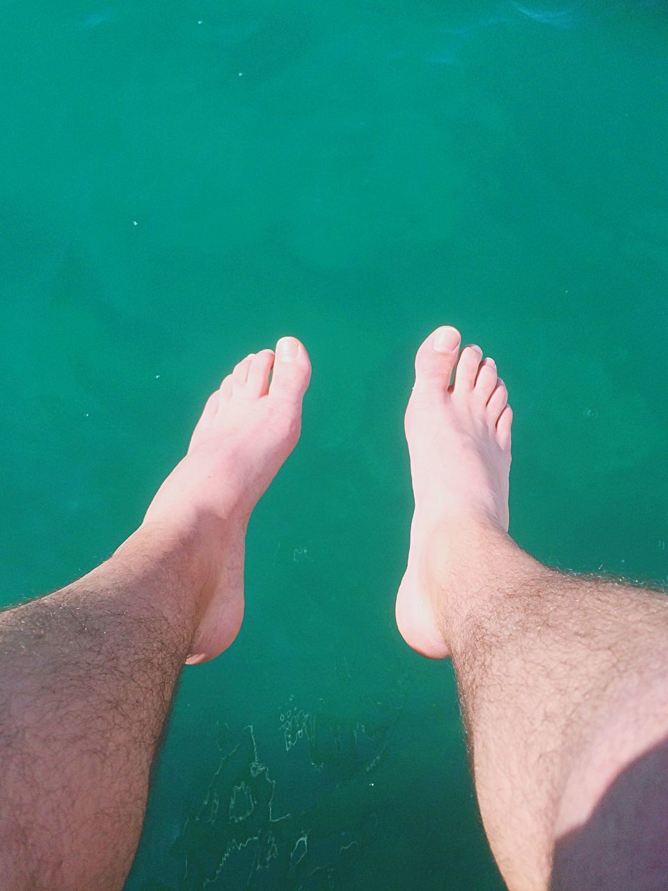 human leg, low section, real people, barefoot, water, human foot, human body part, leisure activity, two people, personal perspective, men, high angle view, day, green color, togetherness, outdoors, close-up