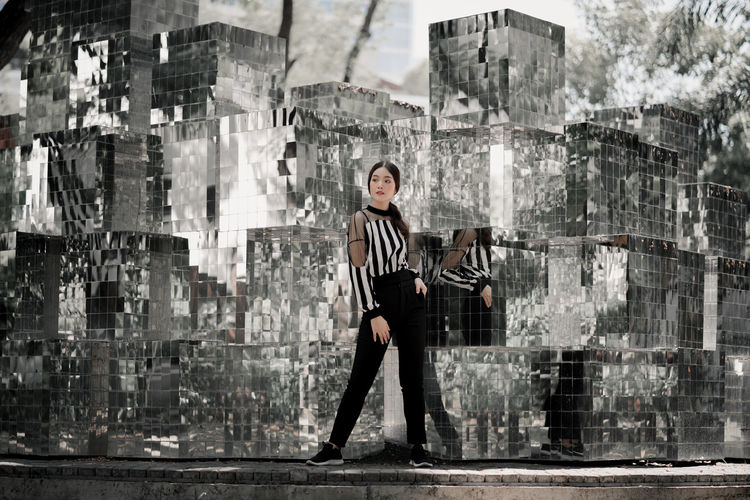 Full length of woman standing against glass structure