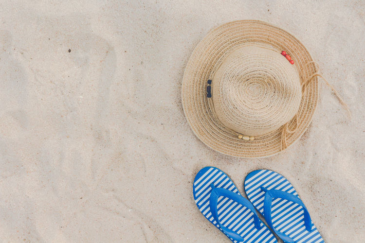 Straw hat and flip flops on a tropical beach Beach Blue Clothing Copy Space Day Directly Above Flip-flop Hat High Angle View Land Lifestyles No People Pair Pattern Personal Accessory Sand Sandal Shoe Slipper  Straw Hat Summer Sun Hat