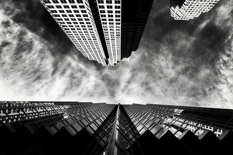 Low angle view of modern building against cloudy sky