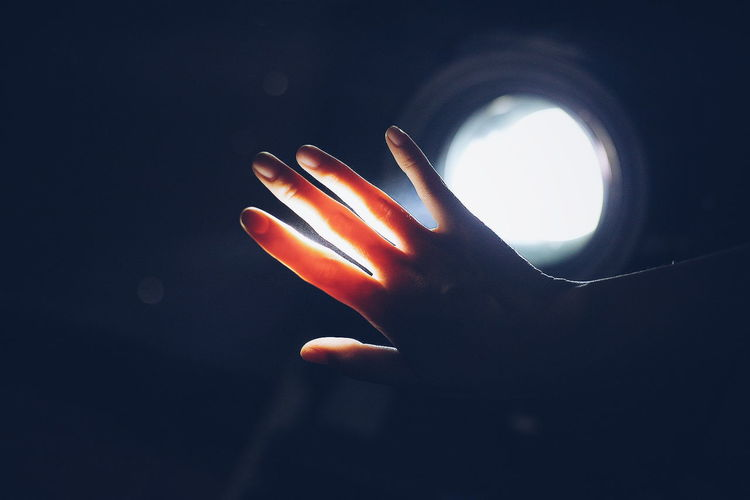 Close-up of illuminated hand against sky