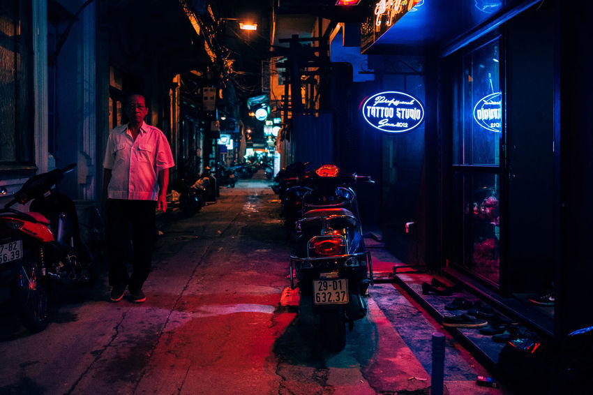 Walking by the Tattoo Shop. Asian Culture Backyard Colors Urban Exploration Architecture Building Exterior Built Structure City Full Length Illuminated Land Vehicle Men Neon Lights Neonlights Night One Person People Real People Rear View The Way Forward Transportation Walking