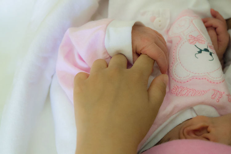 Midsection of baby girl holding mother hand lying on bed
