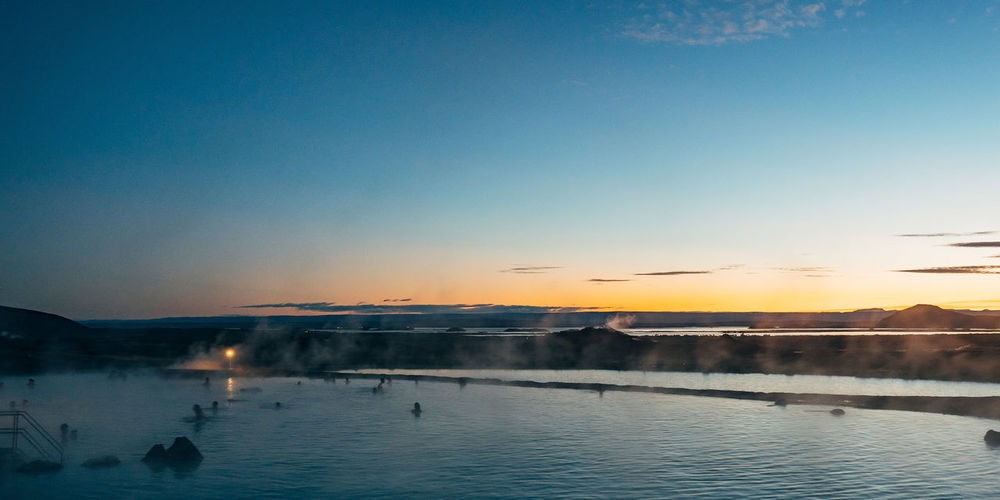 Scenic view of natural spa in iceland against sky at sunset