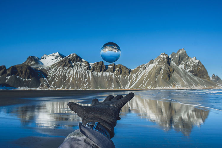 Cropped Hand Wearing Glove While Levitating Crystal Ball By Lake Against Mountains During Winter
