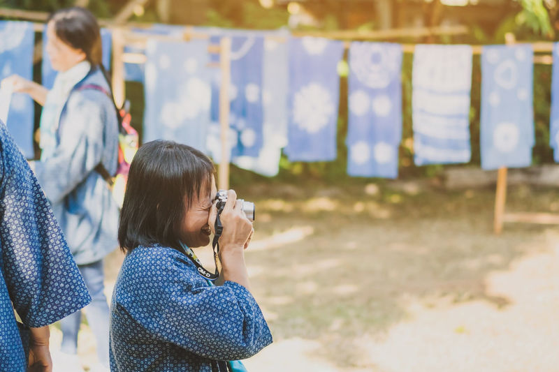 Rear view of girl photographing outdoors
