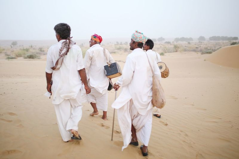 Rear view of people wearing traditional clothing walking at desert