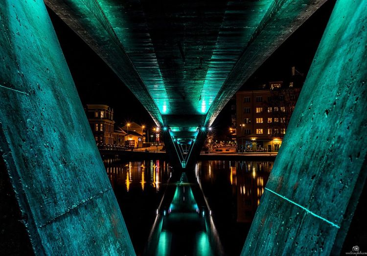 Bridge against illuminated buildings