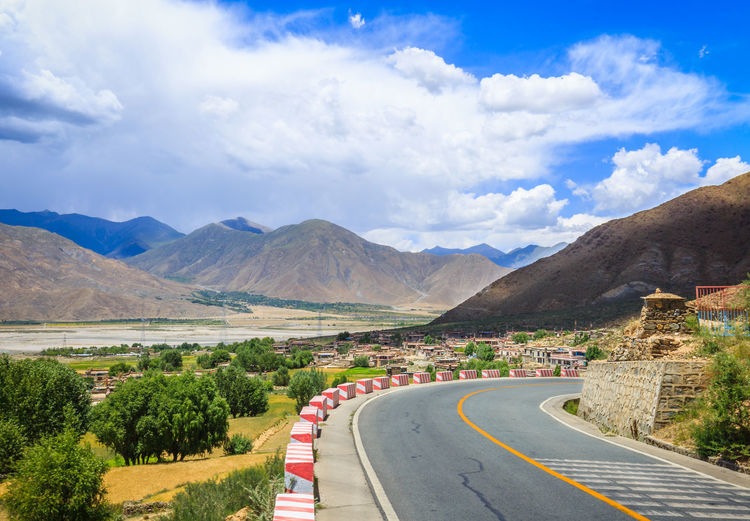Scenic view of road and mountains against cloudy sky