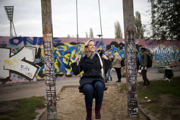 Young woman swinging at playground against sky