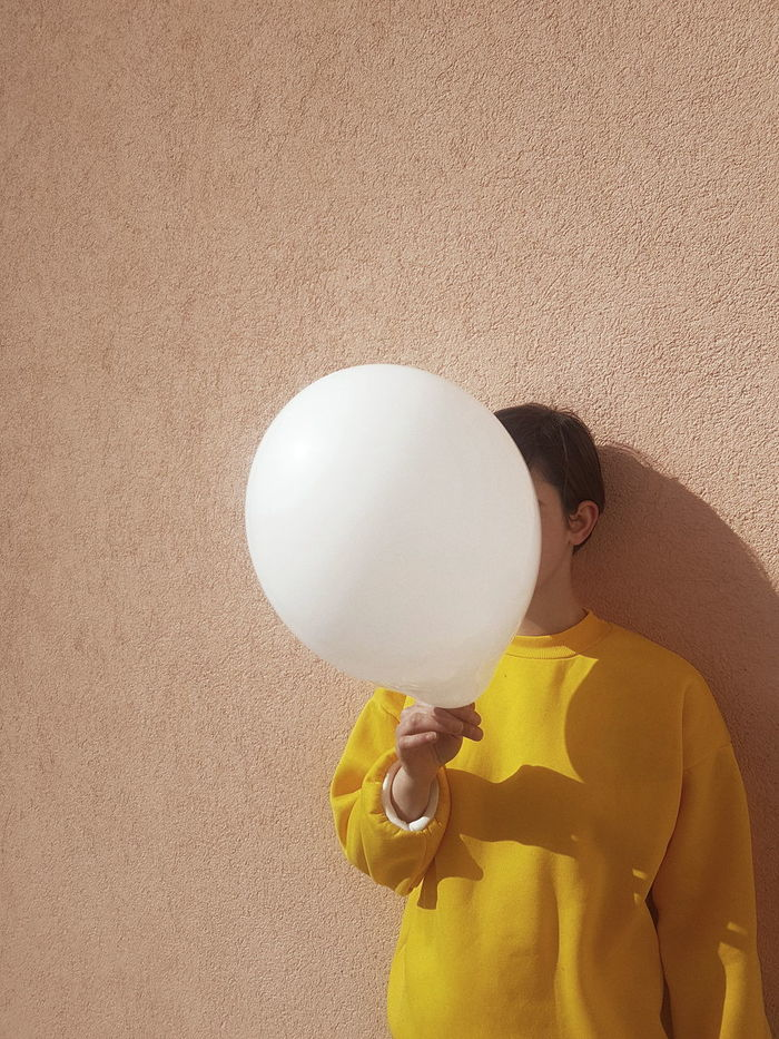 Woman covering face with balloon against wall