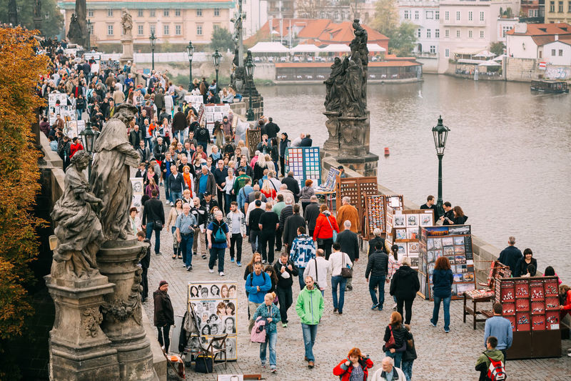 High angle view of people walking on footpath by river in city
