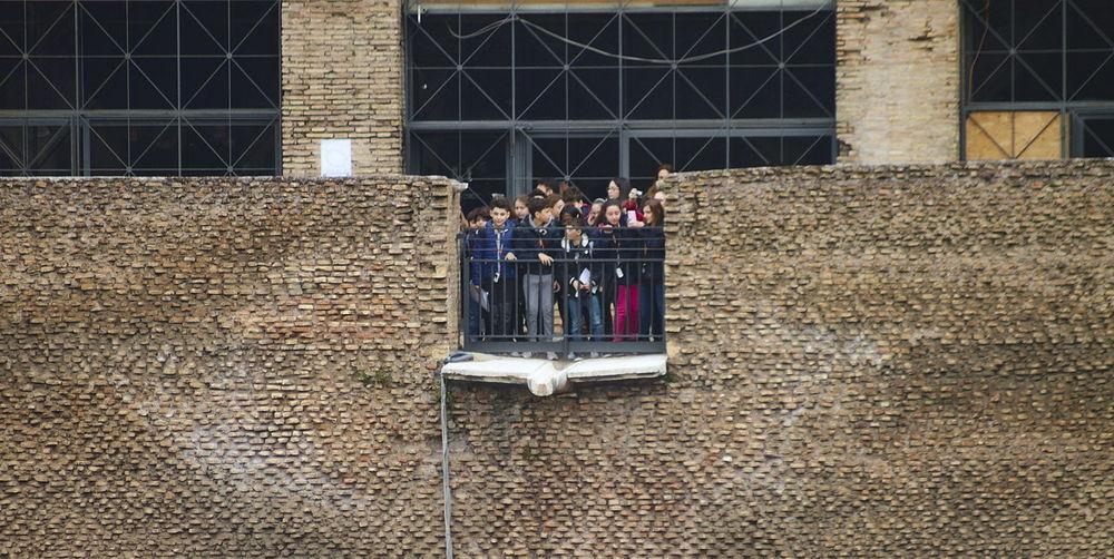 Men standing on brick wall