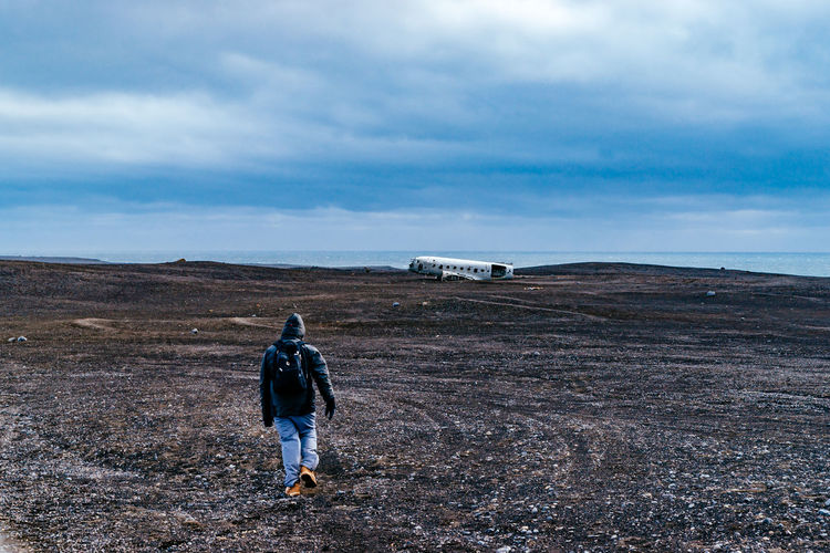 Full Length Rear View Of Man Walking Towards Abandoned Military Airplane At Beach Against Cloudy Sky During Winter