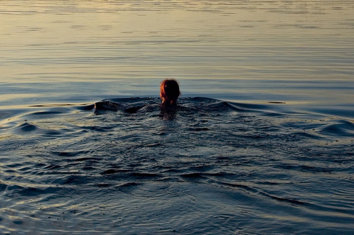 A Finnish Lake A Woman Schwims Beauty In Nature Harmony Leisure Activity Lifestyles Motion Nature One Person Outdoors Peace Of Mind. Pure Nature Real People Sunset Water Waterfront