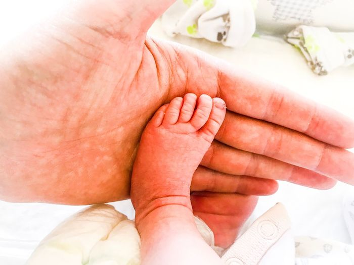 Cropped hand of man touching baby leg at home