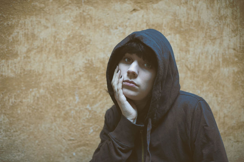 Portrait of sad woman in hooded shirt against wall
